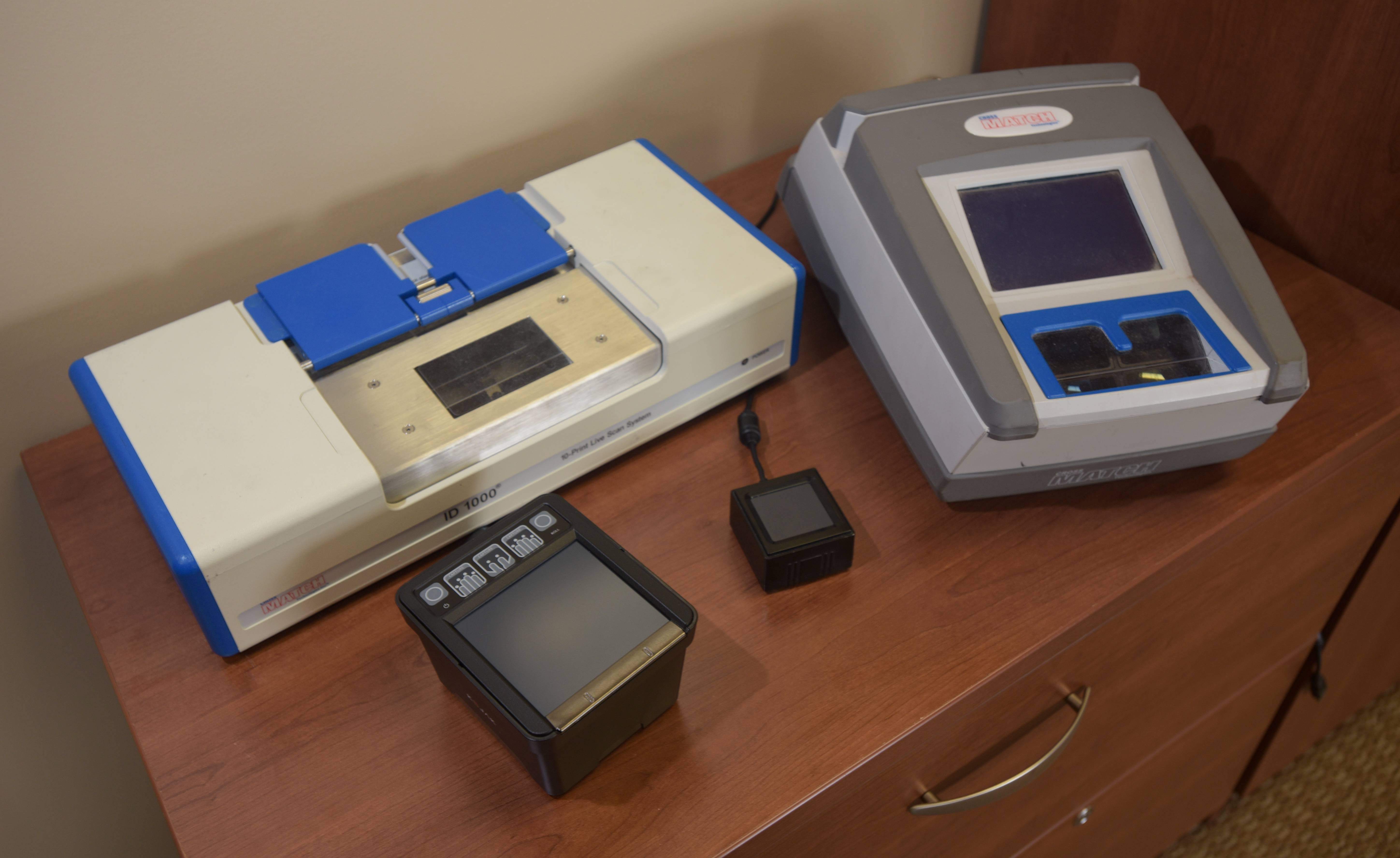 The older and larger fingerprint readers, such as the Cross Match ID 1000 and the Cross Match ID 500, have been replace with the much smaller and lighter newer readers, such as the Integrated Biometrics Kojak and Watson Mini fingerprint readers.