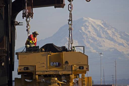 FILE - In this Nov. 4, 2019, file photo a worker prepares a piece of Cat construction equipment made by Caterpillar to be lifted off a trailer at the Port of Tacoma in Tacoma, Wash. Caterpillar Inc. reports financial results Friday, Jan. 31, 2020.