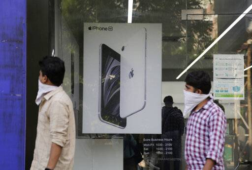 People walk past an image of an iPhone displayed at an Apple store in Ahmedabad, India, Saturday, Aug. 1, 2020. Three contract manufacturers for Apple iPhones and South Korea's Samsung have applied for large-scale electronics manufacturing rights in India under a $6.5 billion incentive scheme announced by the government, Technology Minister Ravi Shankar Praad  said Saturday.